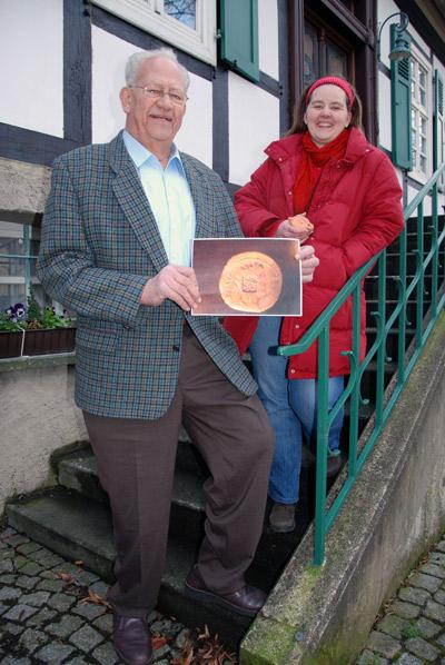 Der Heimatverein Salzkotten beschäftigt sich im Varusjahr auch mit römischer Geschichte: Dr. Walter Hemmen und Manuela Gieseke von Rüden zeigen das Foto einer Militärmünze mit Varusstempel und ein römisches Öllämpchen. (Kopie)